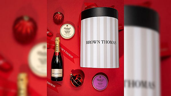 champagne, chocolates and a brown thomas hat box on a red background